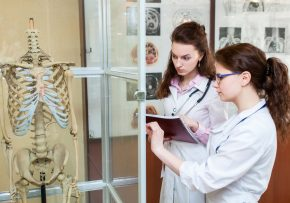 group medical students with skeleton in classroom at university